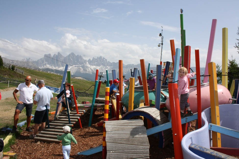 Family walking paths in front of a high alpine scenery